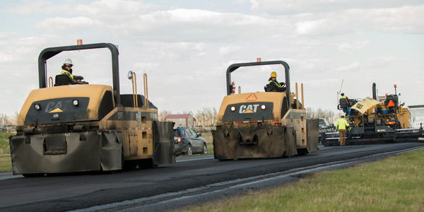 asphalt paver followed by rollers on US Highway 2 east of Devils Lake