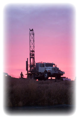 A drill rig on the horizon at sunset
